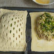 Смазываем тесто вокруг начинки яйцом, кладём надрезанный пласт на начинку, прижимаем края