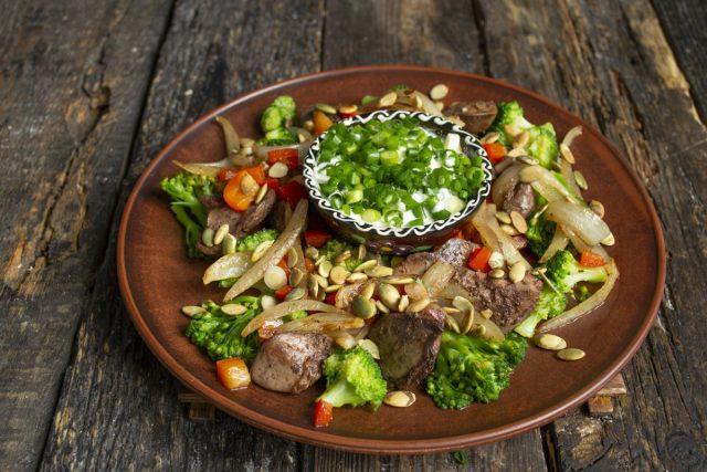 Посыпаем диетический салат из куриной печени с овощами семечками, подаём на стол с соусом