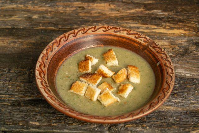 В тарелку наливаем порцию грибного супа-пюре, сверху кладём гренки