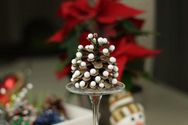 Простая и яркая новогодняя композиция — шишка с приклеенными белыми шариками из наполнителя для игрушек на перевернутом бокале