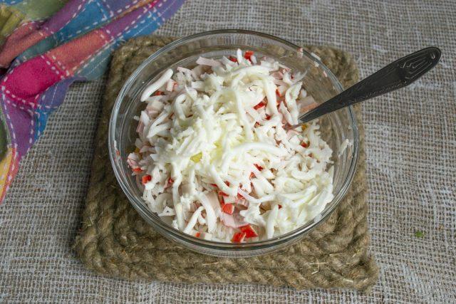 Добавляем измельченные яичные белки, также кладём в салатницу тёртый пармезан