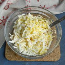 Сваренные вкрутую яйца натираем на крупной тёрке, добавляем к остальным ингредиентам