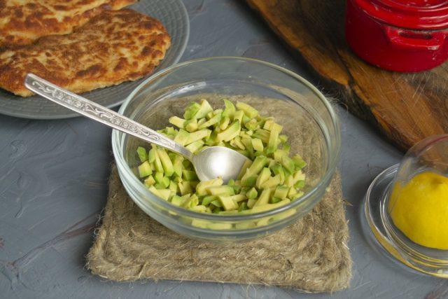 Мякоть авокадо режем мелкими кубиками, кладём в миску, выжимаем сок из половинки лимона
