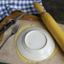 На листе пекарской бумаги раскатываем кусок теста тонко, прикладываем тарелку, вырезаем корж