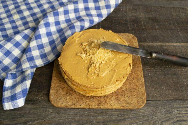 Собранный торт покрываем кремом со всех сторон и посыпаем бисквитной крошкой сверху и по бокам