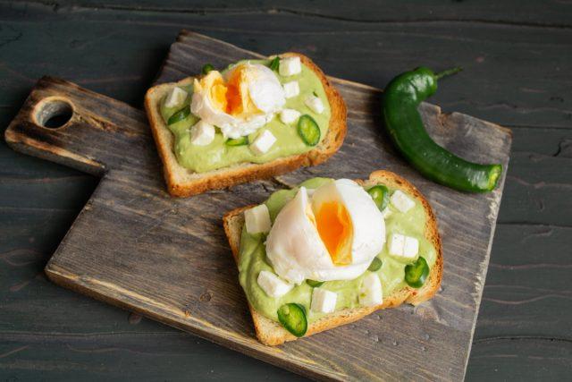 Кладём на тосты яйца пашот, прорезаем ножом посередине