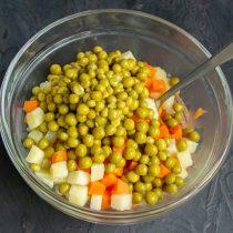 Остывшие овощи кладём в салатник, добавляем консервированный зелёный горошек