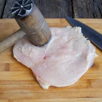 Прикрываем филе пищевой плёнкой, отбиваем молоточком с двух сторон