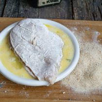 Кладём шницель в тарелку со взбитым яйцом и перекладываем в панировочные сухари