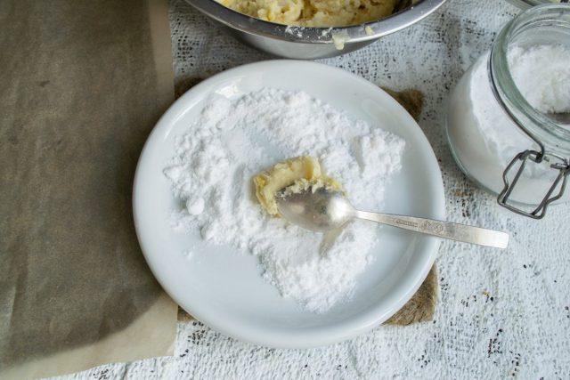 Чайной ложкой зачерпываем охлажденное тесто, кладём в тарелку с сахарной пудрой, скатываем шарик