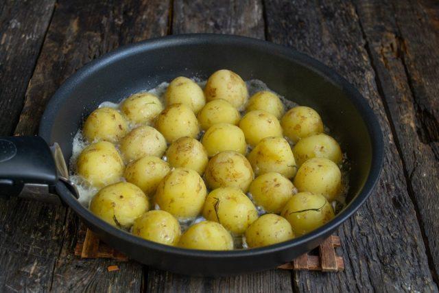 Кладём на сковородку с маслом разрезанные пополам картофелины срезом вниз, жарим 7-8 минут на среднем огне