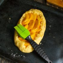 Приподнимаем края и загибаем их на начинку, обильно смазываем фрукты растопленным маслом