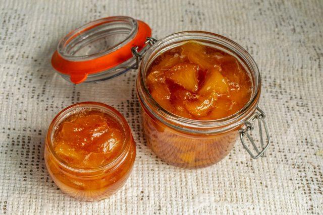 Готовый персиковый джем с лимоном и лимонной цедрой раскладываем в сухие банки и плотно закрываем