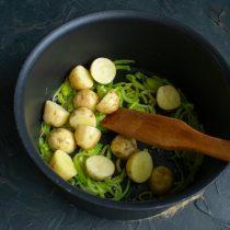 Отмытую мелкую молодую картошку разрезаем пополам, кладём в кастрюлю к обжаренному порею
