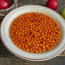 Собранные ягоды облепихи пересыпаем в миску, заливаем холодной водой