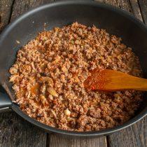 Добавляем к гречке фарш с приправами, добавляем воду, соль и перец