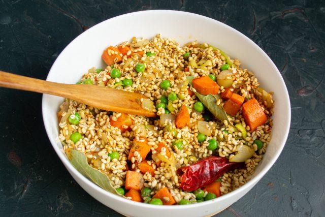 Перемешиваем овощи с крупой и выкладываем в форму для запекания