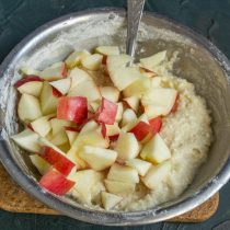 Tăiați merele dulci în cuburi mici, puneți-le în aluat și amestecați