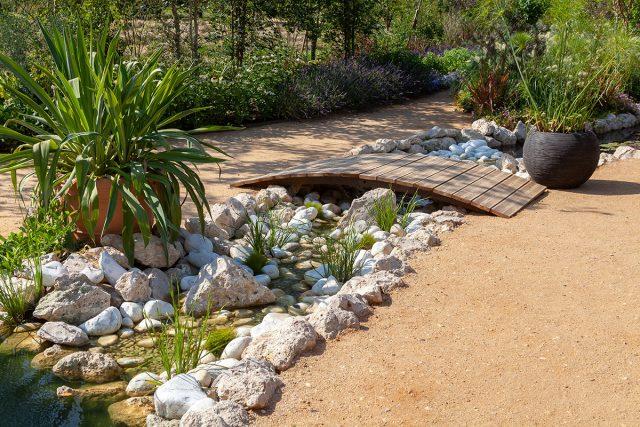 Вариант оформления ручья с помощью камней, растений и мостика