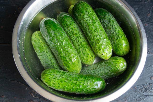 Кладём огурцы в миску или таз и заливаем холодной водой