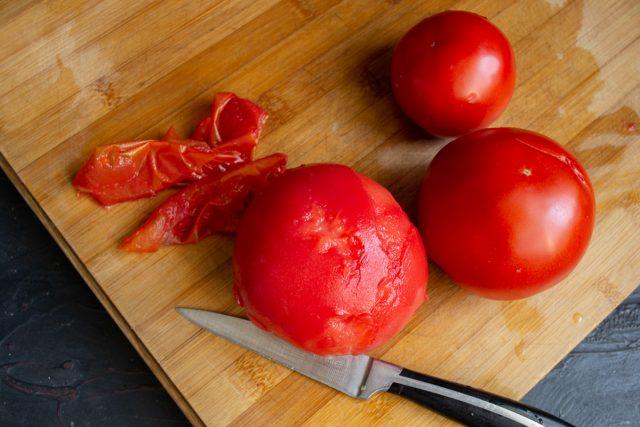 Снимаем кожицу с помидоров, вырезаем уплотнение с плодоножкой
