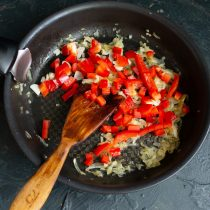 Cortar los pimientos morrones y agregarlos a las cebollas fritas.