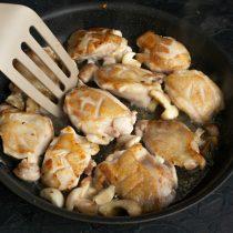 Добавляем грибы и измельченный чеснок, обжариваем пару минут и выкладываем в тарелку