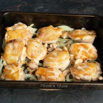 В форму выкладываем обжаренный лук, затем куриные бёдра и грибы