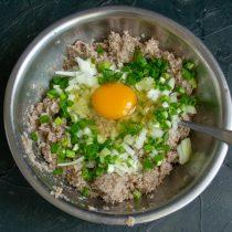 Лук посыпаем солью, сверху разбиваем куриное яйцо